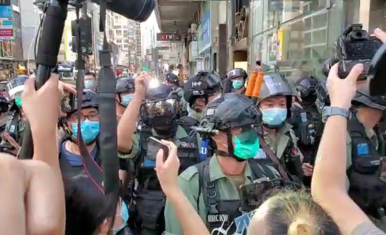 油麻地,彌敦道與咸美頓街交界,有防暴和記者發生爭論。後面一警員用LED電筒照射記者。(影片截圖  宋碧龍 / 大紀元)