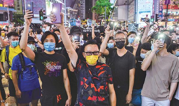 ██6月12日「反送中」運動一周年,市民在銅鑼灣高唱《願榮光歸香港》時,點亮 他們的手機。(ANTHONY WALLACE / AFP via Getty Images)
