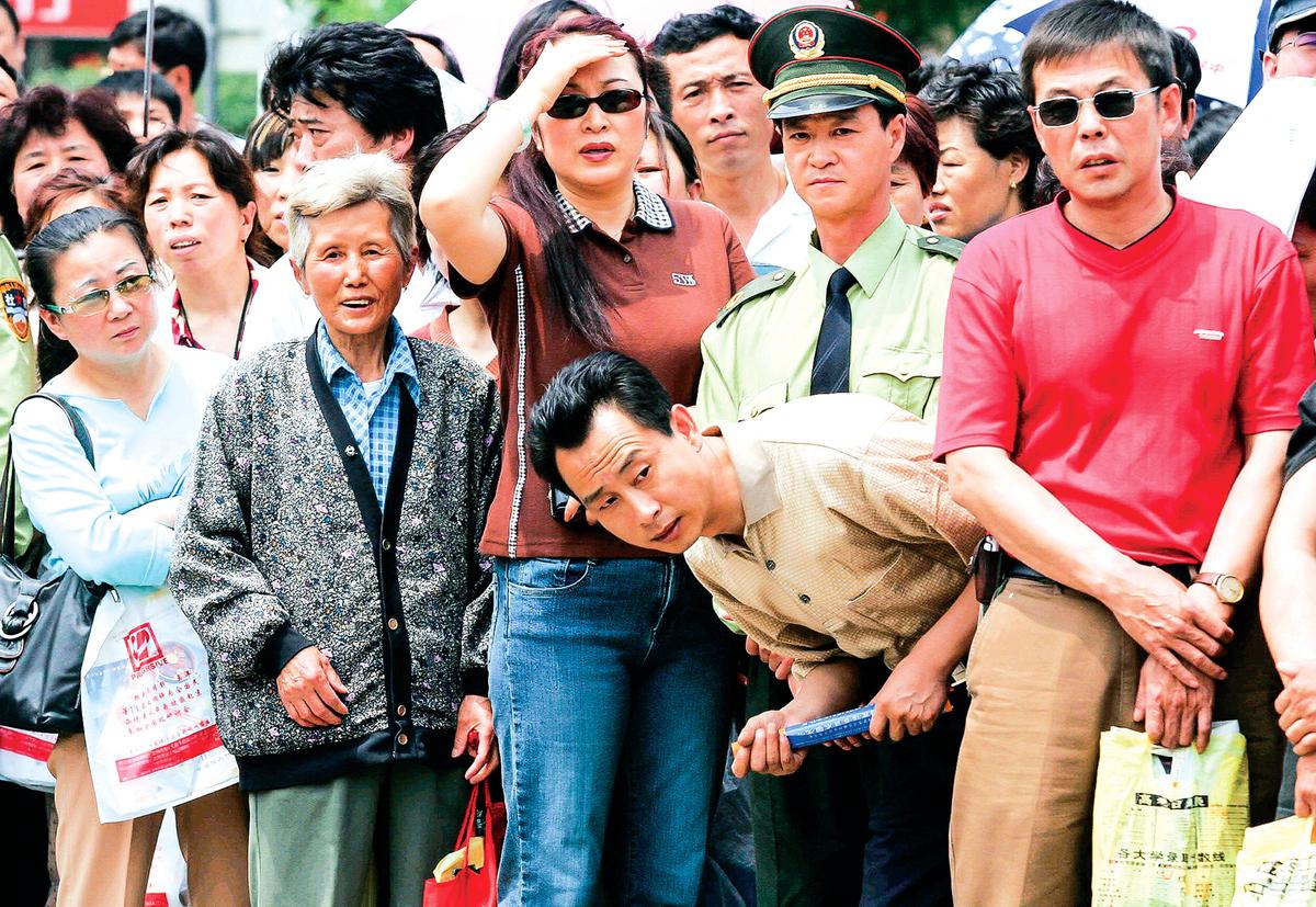 在中國高考考生多,競爭十分激烈,被形容為「千軍萬馬過獨木橋」。圖為2005年6月8日在遼寧省瀋陽市的某大學入學考場外,急切等候的考生家長們。(Getty Images)