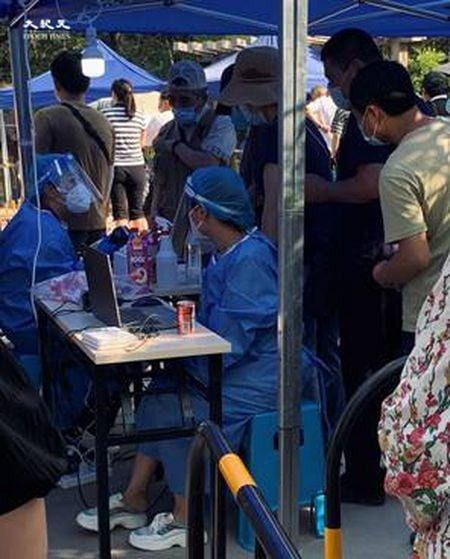 2020年6月30日下午四點,田村山核酸檢測點身份證登記處,五個人給一個裝棉籤的小瓶子。(大紀元)