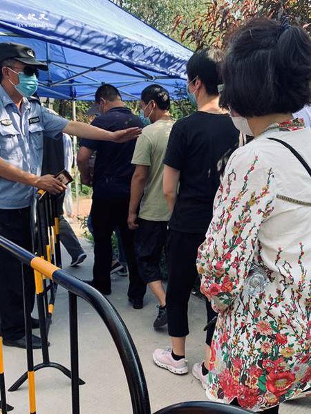 2020年6月30日下午四點,天氣炎熱,田村山核酸檢測點,保安在進行五個人分組。周圍的人說:「他這個是五個五個一組,五個人都做,五個棉籤放一個裏頭,為了提高檢測效率,要是一個人有毛病,這五個人都跑不了。」(大紀元)