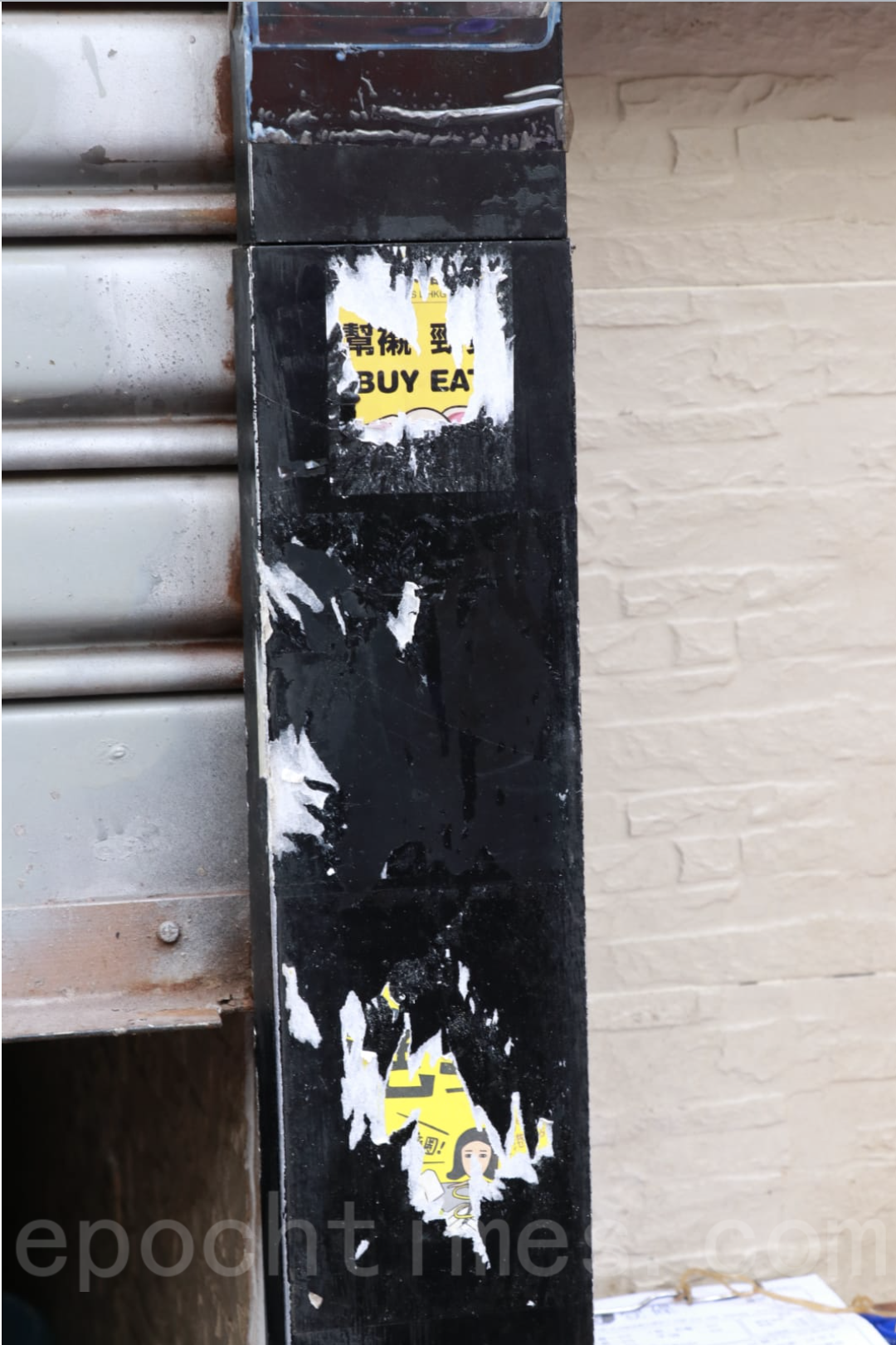 「壹碗壹碟」店外兩張「香港人米豬連美食指南」貼紙,縱使毫無政治訊息,仍遭撕去。(杜夫/大紀元)