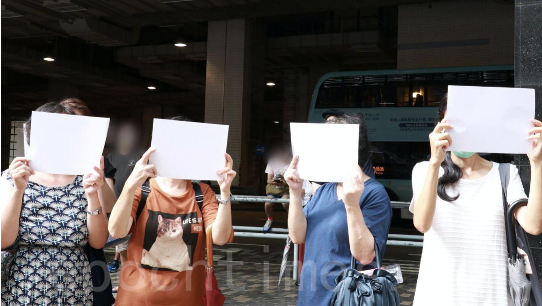 到法庭聲援抗爭者的婦女感到「港版國安法」條文含糊,標語、口號動輒足以入罪,只能高舉白紙以表不滿。(杜夫/大紀元)