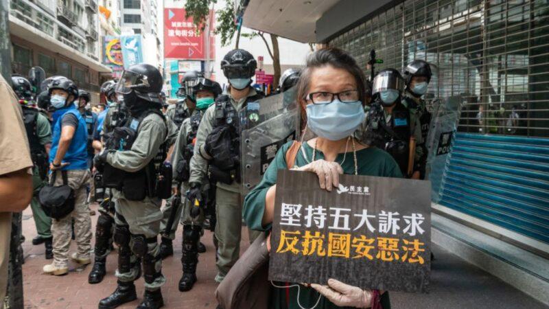 2020年7月1日,香港市民自發舉行了反對「港版國安法」的示威遊行。圖為一名婦女在一隊警員前面展示標語牌。(Anthony KwanGetty Images)