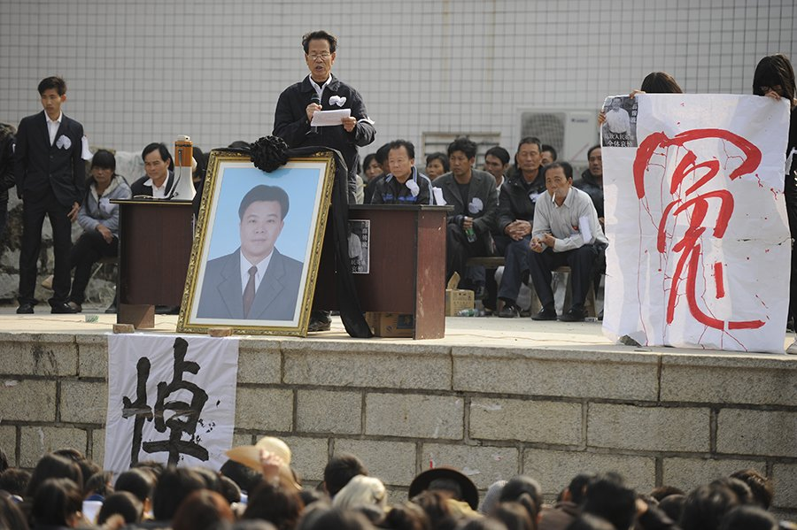 2011年12月16日,烏坎村民舉行集會及為被打死村民代表薛錦波辦追悼會。中間站立在薛錦波遺照後者為林祖鑾。(AFP ImageForum)