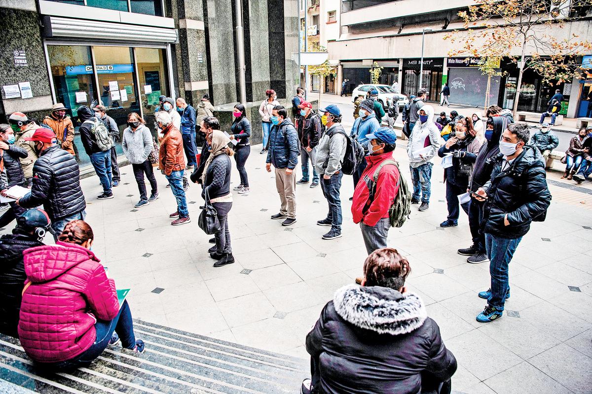 目前智利疫情形勢不容樂觀,僅次於巴西和祕魯。疫情也加劇了智利的經濟危機,使許多人沒有了生計。圖為5月28日,在智利失業基金管理局總部的門口,人們排隊等候領取失業救濟金。(Getty Images)