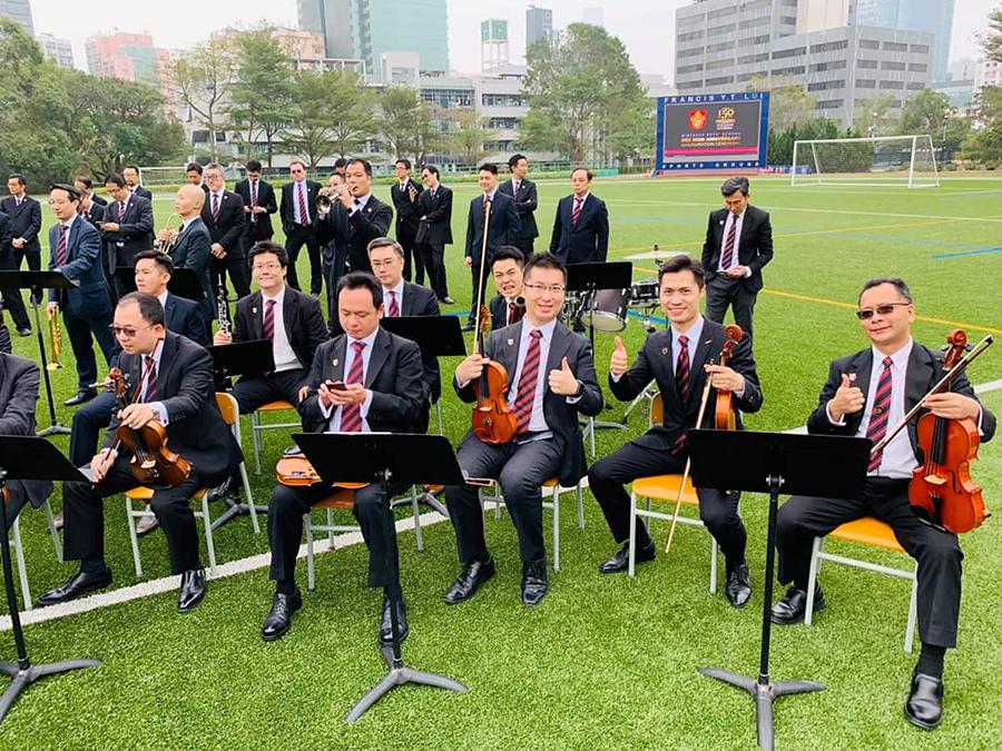拔萃男書院150週年校慶期間,Roy(右前三)與一眾校友組成的管弦樂團一起於校園草地上演奏。(受訪者提供)