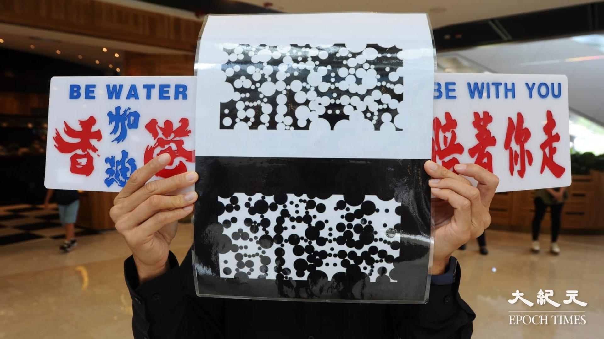 有手持異體字的「光復香港,時代革命」的標語遭到盤查並被攝錄,並反覆將異體的「光復香港,時代革命」進行攝錄。(宋碧龍 / 大紀元)