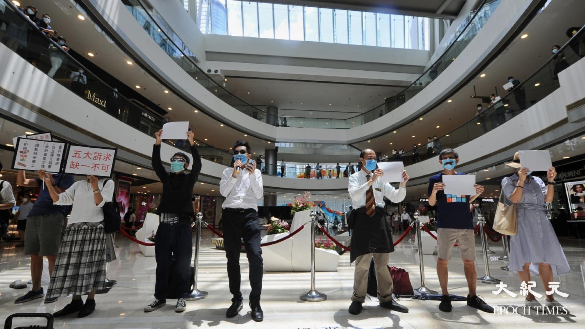 今日(7月6日),數十位抗爭者來到IFC(國際金融中心)進行「國安法」後的首次「和你Lunch」。智慧的香港人這次則用數字、用無字天書、用異體字等另類方式表達訴求,仍然可唱《願榮光歸香港》,而抗爭的訴求仍然圍繞「五大訴求,缺一不可」,另類方式並無損他們爭取民主自由的決心。(宋碧龍 / 大紀元)
