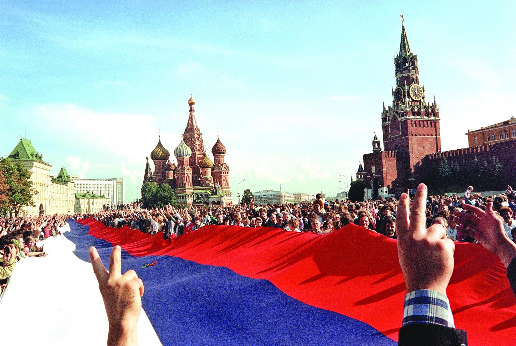 1991年8月22日,在莫斯科紅場,人們拿著一幅巨大的俄羅斯國旗慶祝蘇共解體。(AFP)