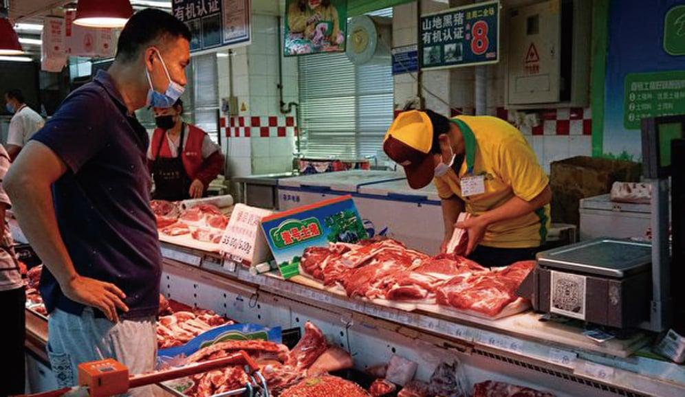 大陸豬肉價格連續5周上漲。2020年6月中國北京,一名戴口罩的顧客在超市買豬肉。(Getty Images)