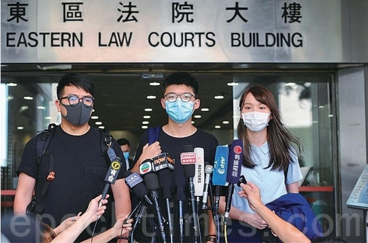 就去年6月21日前香港眾志秘書長黃之鋒、主席林朗彥及成員周庭因涉嫌包圍警察總部遭檢控,三人均被控以煽惑他人參與未經批准集結及參與未經批准集結等3項罪名,並於昨日(7月6日)在東區裁判法院再訊。圖為黃之鋒、周庭、林朗彥三人步出東區法院。(大紀元)