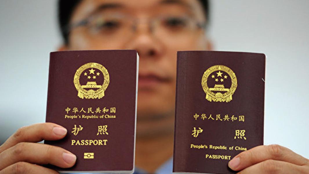 中國6類在職公職人員持有國外永居證、外國國籍將受到記過或撤職開除等不同程度的處分。圖為一名民警展示新版護照(左)和舊版護照。(大紀元)