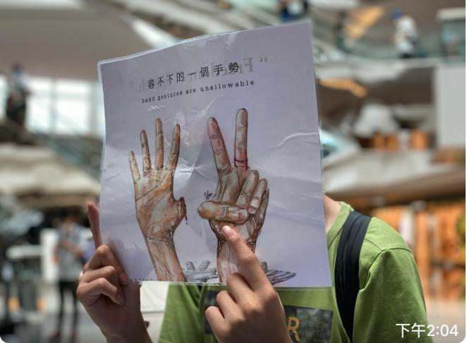 舉起的牌上寫著「容不下的一個手勢」。7.9西九龍「和你Lunch」活動中,少數抗爭者在九龍塘又一城喊口號,唱「數字歌」。(霄龍 / 大紀元)