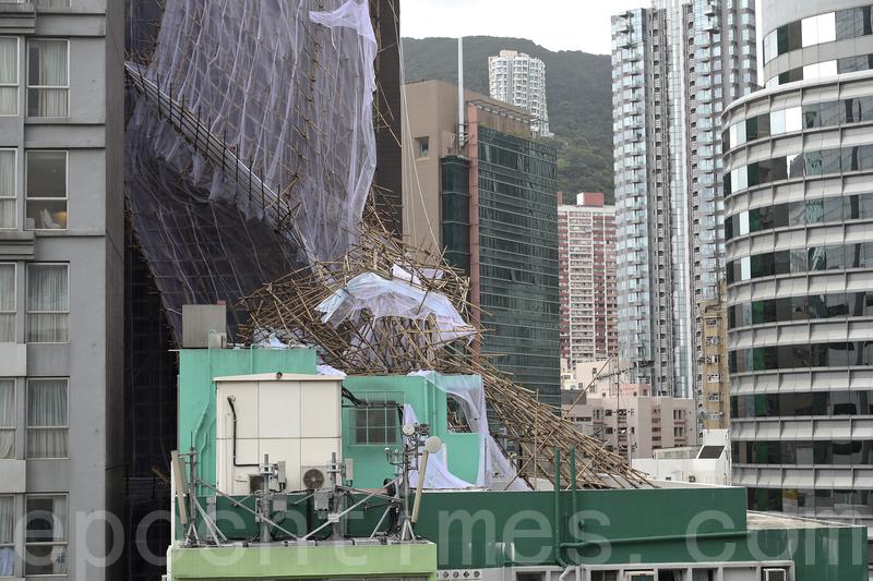 颱風「妮妲」吹襲香港期間,灣仔菲林明道7號一幢商業大廈外牆約10層樓高的棚架倒塌,運輸署一度將軒尼詩道往中環方向近菲林明道的全線封閉。(余鋼/大紀元)