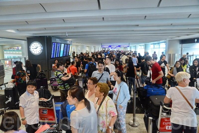 受颱風影響,數以千計的旅客滯留機場,昨日機管局重編配500班來往香港的航班。有航空公司櫃位以拉帶圍欄分隔人潮。( 宋祥龍/大紀元)