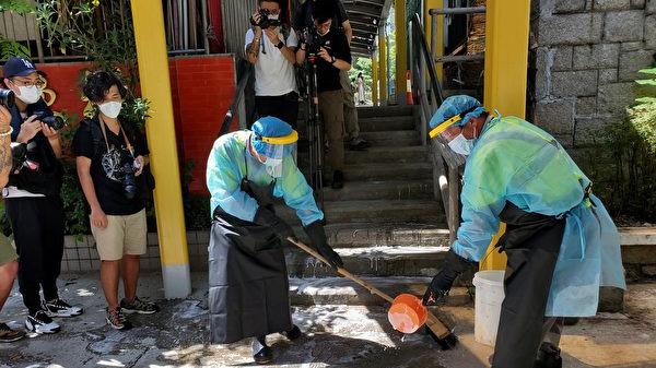 圖為7月7日,中華基督教會扶輪中學有學生確診,食環署外派清潔工消毒清潔校門及行人路。(大紀元圖片)