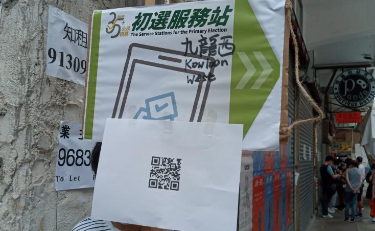 街頭的路標。遠處可見人群低頭在手機操作,進行電子投票。(梁珍 / 大紀元)