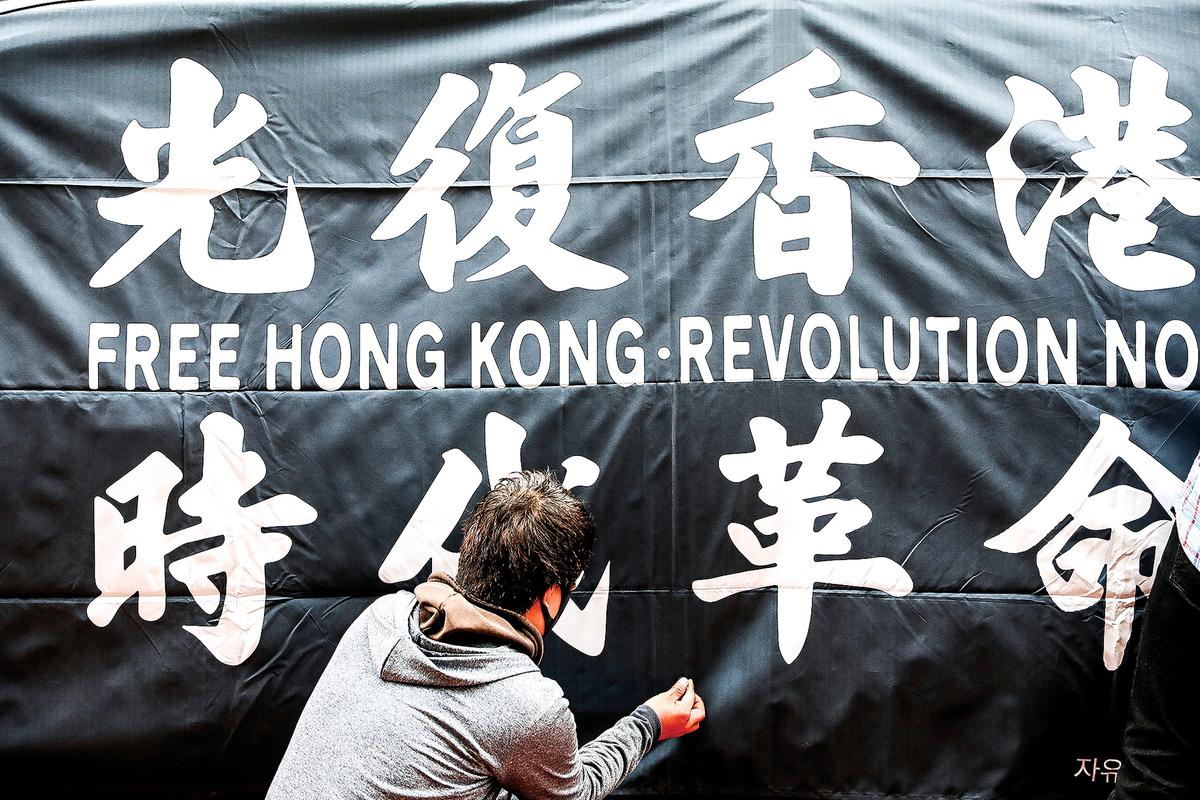 儘管港府在國安法下把「光復香港,時代革命」定性為非法,但這個口號正被國際社會「傳承」。圖為7月7日,韓國首爾的抗議者在中共駐韓國大使館前展示「光復香港,時代革命」橫幅,聲援香港人。(Getty Images)