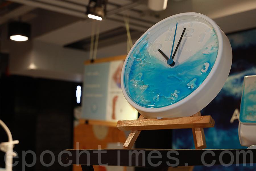 白色時鐘上,Yucca運用樹脂,將流動的藍色波紋凝固在時鐘的表面,表現出海洋的型態。(陳仲明/大紀元)
