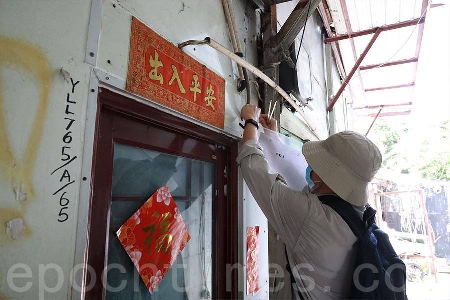 有村民表示,地政總署人員今早鬼崇地逐家逐戶在門外張貼告示,並未敲門與村民溝通。(陳仲明/大紀元)