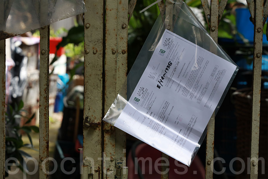 地政總署人員今早在橫洲三村逐家逐戶張貼告示,勒令村民於7月29日搬走。(陳仲明/大紀元)