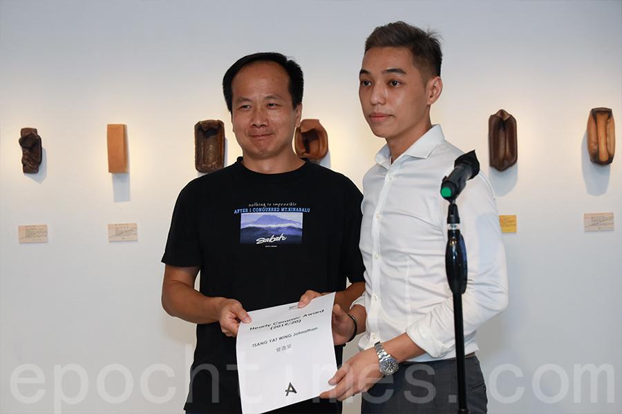 曾逸榮(左)用自己的陶瓷塑像從模糊變清晰,影射這些年來香港遇到的大事件,如何一步步認識香港人的身份。(陳仲明/大紀元)