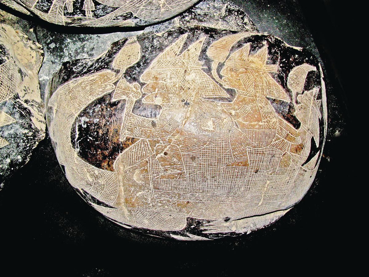 石頭上雕刻著3個人騎在一隻恐龍的背上,前面的人雙手拿著斧頭形狀的工具。(網絡圖片)