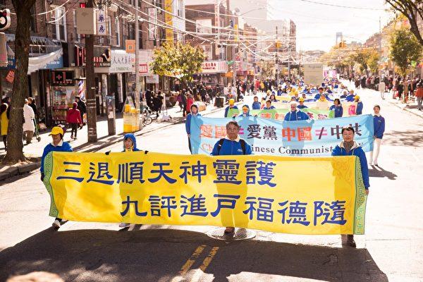 2018年10月21日,紐約部份法輪功學員近千人在布碌崙八大道舉行盛大遊行,市民紛紛駐足觀看。橫幅上寫:「三退順天神靈護, 九評進戶福德隨」(戴兵/大紀元)
