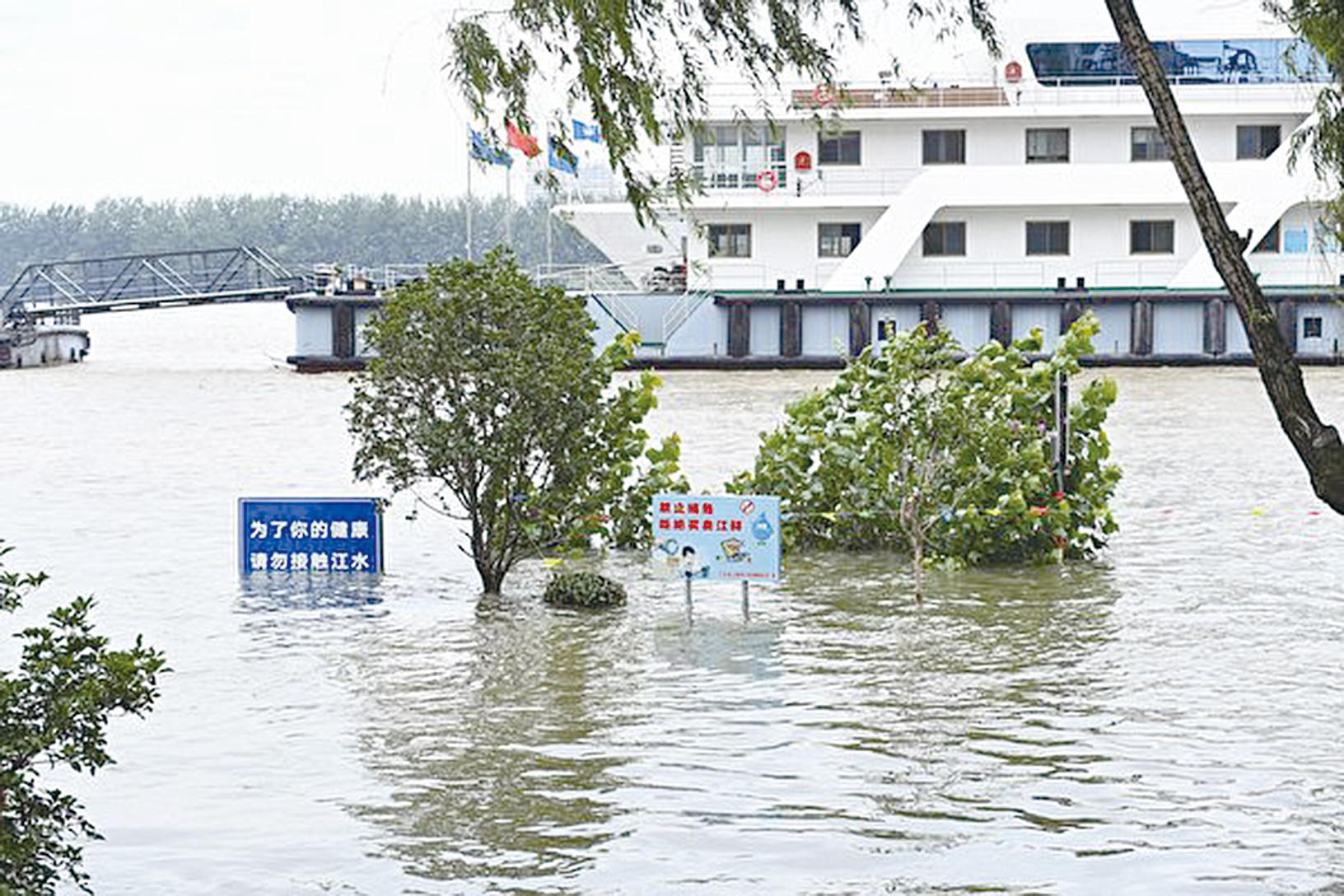 2020年7月12日,中國江蘇省南京市,長江水位高漲,周遭標誌一部份淹沒在水面之下。(STR/AFP via Getty Images)