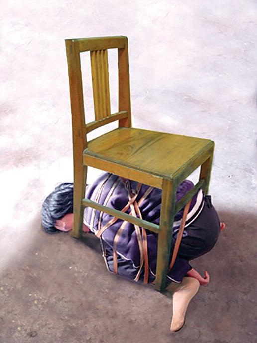 北京女子監獄酷刑模擬:五花大綁塞椅子底。(明慧網)