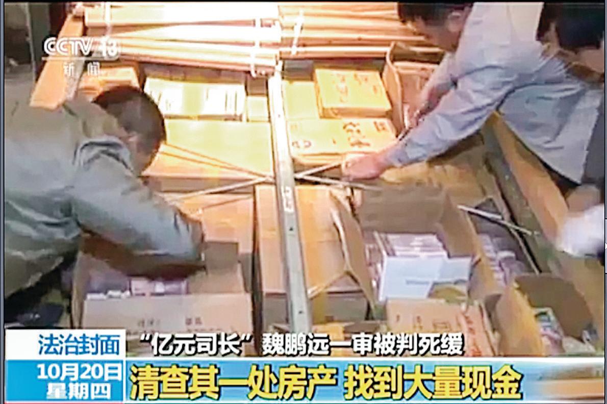 中共連出「億元巨貪」。圖為前國家能源局煤炭司副司長魏鵬遠家藏現金逾2億,被當局查抄。現金放滿了屋內床墊下的紙箱。(影片截圖)
