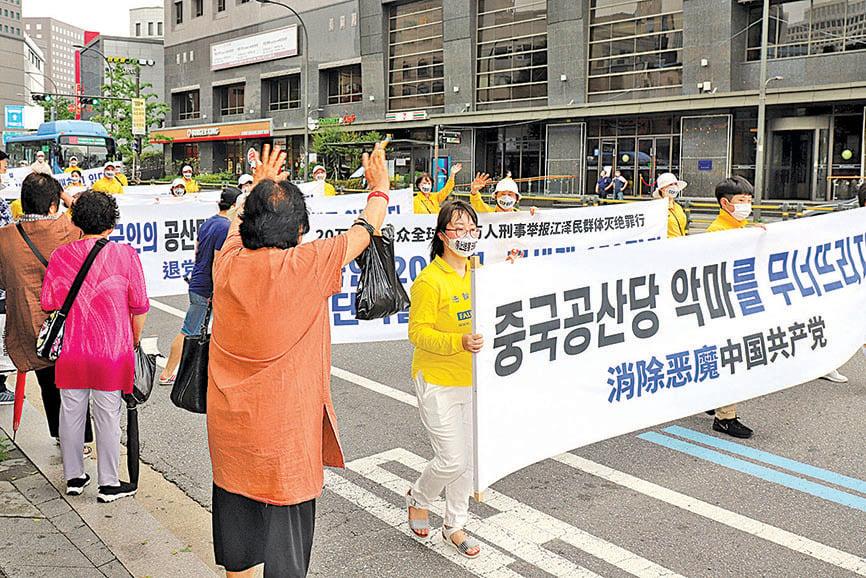 一位民眾向遊行隊伍揮舞手臂表示歡迎,並連連高喊「我們國家有救了。」(金國煥/大紀元)