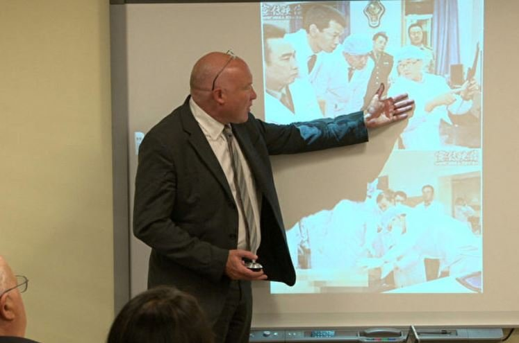 美國資深中國分析人士葛特曼(Ethan Gutmman)在華盛頓展示「王立軍身穿白袍在錦州市公安局現場心理研究中心現場進行解剖研究指導」的照片。那裏涉嫌參與活體摘取法輪功學員器官。(方明/大紀元)