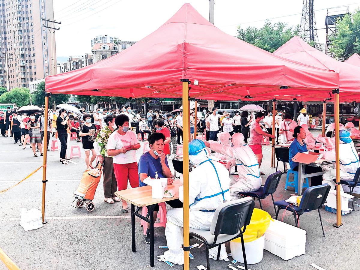 遼寧省大連市疫情又起並擴散到周邊省份。圖為7月26日,人們在大連市的一個停車場的臨時測試中心排隊,接受中共病毒測試。 (Getty Images)