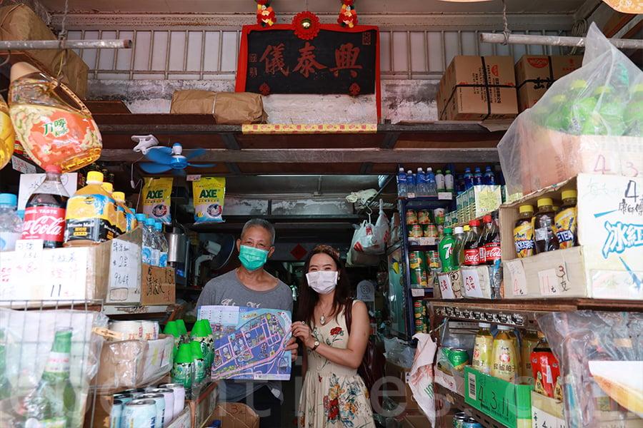 興泰儀老店跨越兩個世紀,慧惠將小店記錄在鴨脷洲社區地圖中,贈送地圖給老闆盧先生(左)。(陳仲明/大紀元)