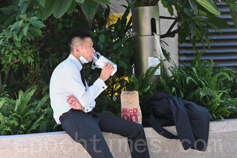 7月29日,全日「禁堂食」第一天,本港所有餐廳不能坐人,市民只能外賣,在路邊進食。(宋碧龍/大紀元)