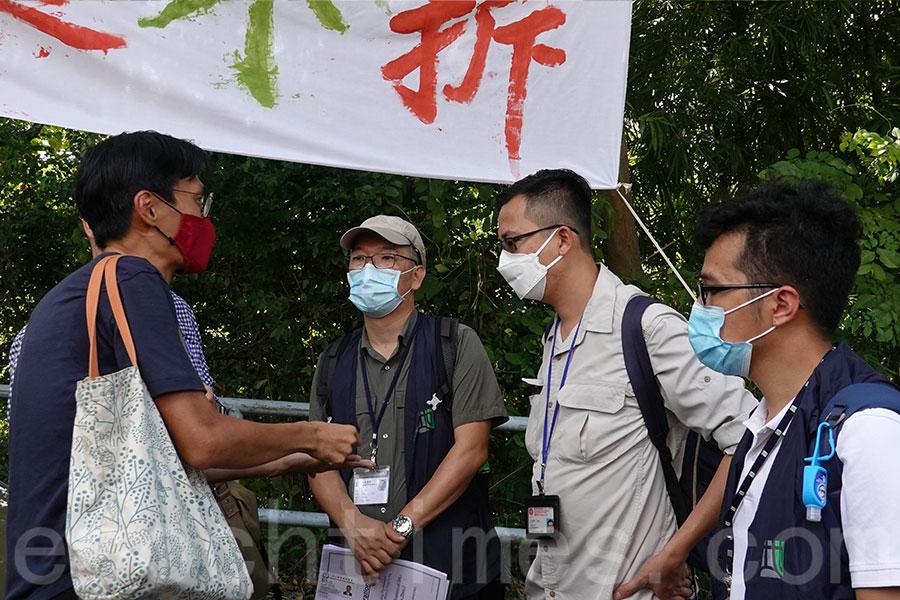 立法會議員朱凱廸與地政總署人員對話,促請他們聆聽村民聲音,在解決所有村民的安置問題後再清拆。(曾蓮/大紀元)