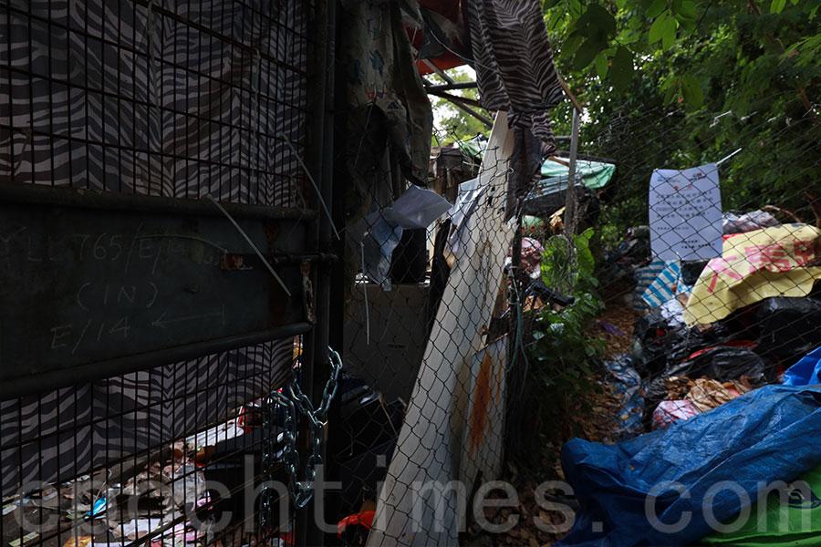 政府人員將圍封的村屋上鎖,並在屋前通道圍上鐵絲網及貼上告示。(陳仲明/大紀元)
