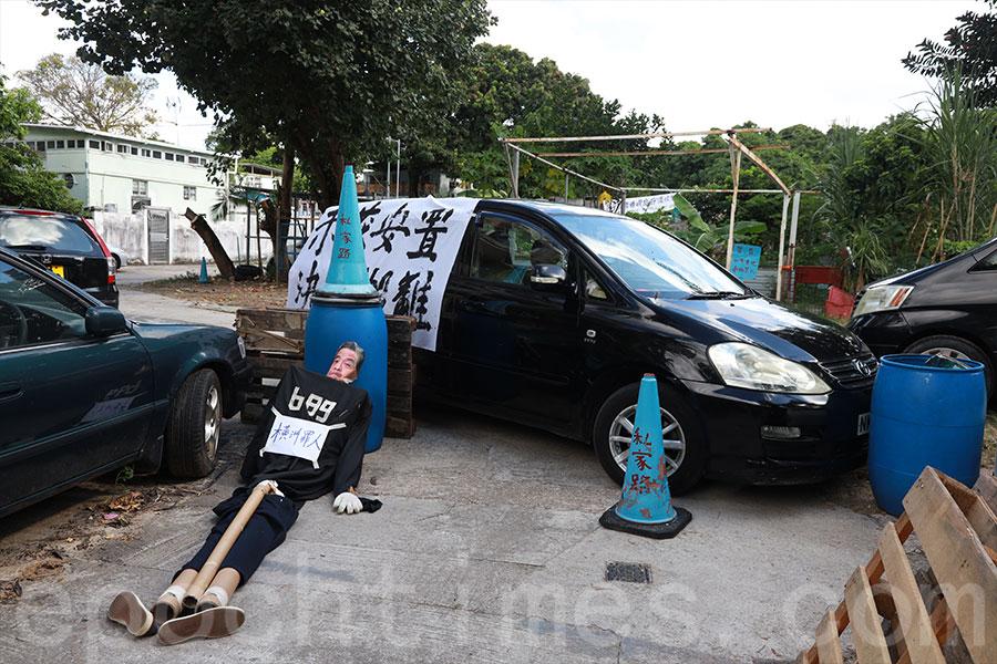 鳳池村有村民以私家車及雜物阻塞道路,企圖阻止政府人員進入收地。(陳仲明/大紀元)