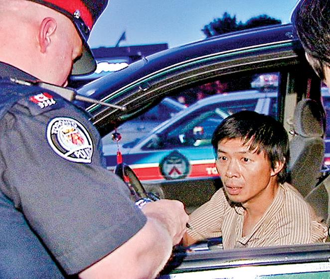 2007年6月30日,多倫多警方訊問魯平,他在多倫多東北部的Asian Farm雜貨店發放Les Presses Chinoises發行的反法輪功小報。(NTDTV)