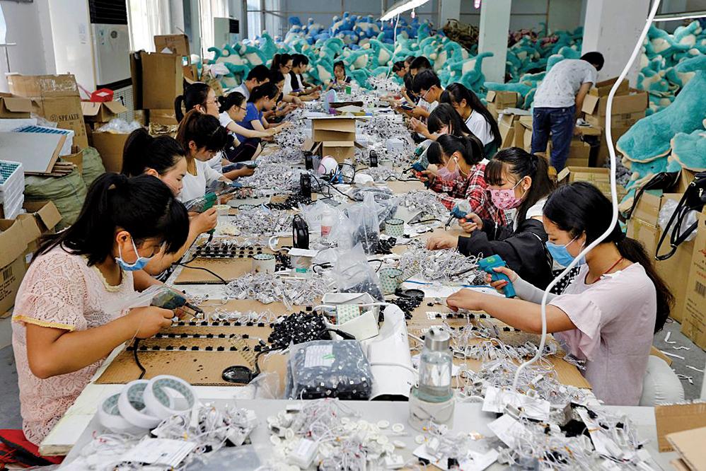 圖為中國江蘇省連雲港市一家玩具廠裏,工人正在製作毛絨玩具。 (AFP)