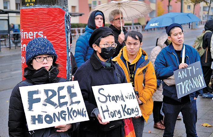 █ 2 0 1 9 年 11 月9 日, 德國柏林圍 牆推倒30 周年, 一 批人在圍牆遺址前, 持支持香港抗爭的標語牌。(Sean Gallup/Getty Images)