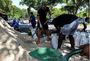 圖為佛州人在裝沙袋,為颶風做好準備。(AFP)