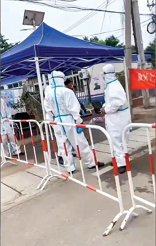 北京大興區疫情爆發點由穿防護服的看守。(視頻截圖)