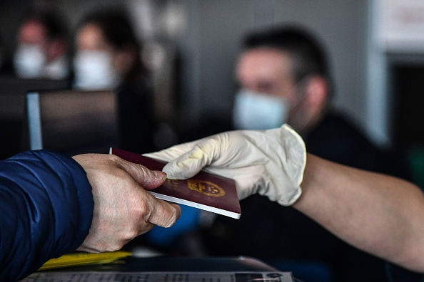 持中國護照出國。示意圖。(TIZIANA FABI/AFP via Getty Images)