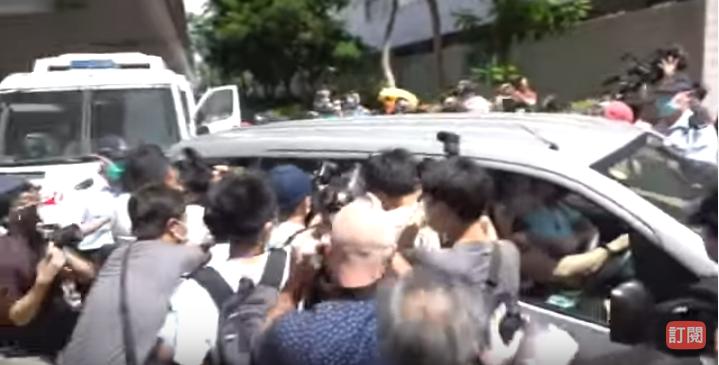 7月6日,載有「國安法」首名被告的車輛到達法院,大批記者一擁而上。(影片截圖)