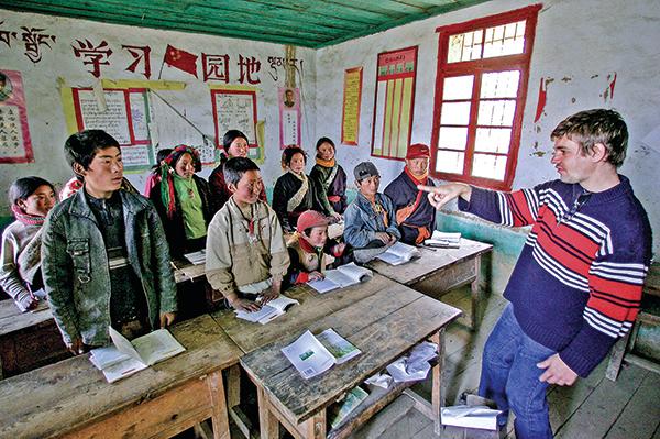 一位英國遊客在2005年4月15日在中國四川省甘孜藏族自治州康定縣的香農小學教藏族學生學習英語。(Getty Images )