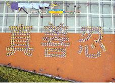 超過五百名法輪功學員身穿黃衣白褲,16日清晨聚集在香港中環愛丁堡廣場,排出「真善忍」三個大字。(大紀元)