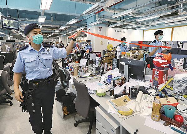 █ 多名警員曾肆意翻閱記者 桌上的文件資料, 明顯侵犯報社的法 律權益, 也超越 手令權力範圍。 (Handout/Getty Images)
